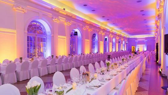 Farblich passend zum Hochzeitskonzept beleuchteter Festsaal der Große Orangerie